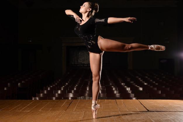 Śliczna baletnica w pointach stoi na scenie robiąc klapkę nogawki