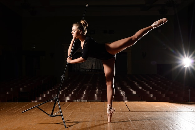 Śliczna baletnica w pointe butach robiących klapkę nogi trzymającej się za ręce na stojaku na scenie