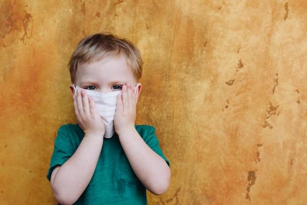 Śliczna berbeć chłopiec jest ubranym ochronną medyczną twarzy maskę