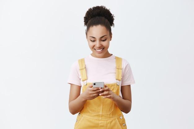 Śliczna, beztroska dziewczyna układa harmonogram na jutro dzięki nowej aplikacji. portret uroczej miejskiej kobiety o ciemnej skórze w żółtym kombinezonie, trzymającej smartfon, uśmiechającej się do ekranu podczas pisania wiadomości
