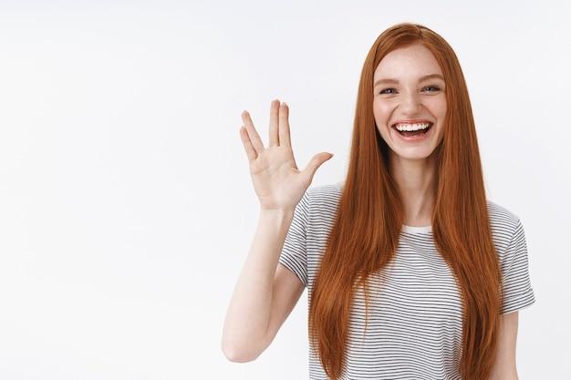 Śliczna beztroska młoda rudowłosa nastoletnia geek dziewczyna lubi oglądać seriale fan fantazy filmy pozdrawiam przyjaciół podnosząc rękę pokaż gest spok uśmiechając się szeroko baw się dobrze witając gości przyjęcie, biała ściana