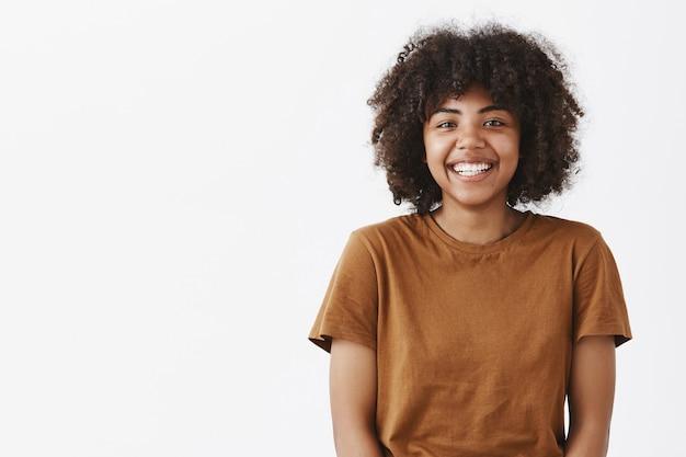 Śliczna, beztroska, przyjaźnie wyglądająca afroamerykanin nastolatka z fryzurą afro, szeroko uśmiechnięta z nieśmiałym i radosnym wyrazem twarzy spotykająca nowych kolegów z klasy