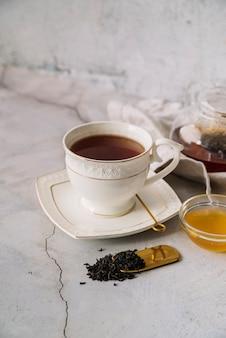 Śliczna biała filiżanka herbata na marmurowym tle