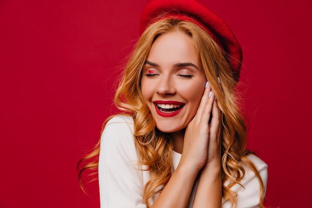 Śliczna biała kobieta w francuskim berecie wyrażająca inspirację. debonair blondynka śmiejąca się z zamkniętymi oczami na czerwonej ścianie.