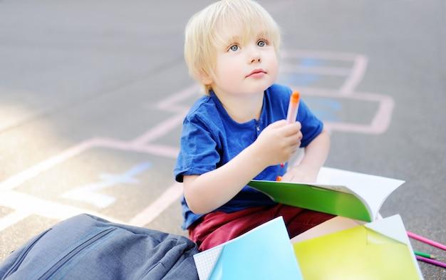Śliczna blond chłopiec robi pracie domowej siedzi na szkolnym jardzie po szkoły z torbami kłaść blisko.