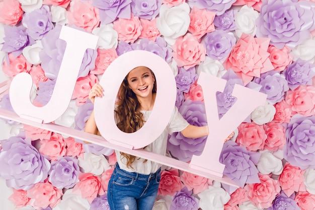 Śliczna blond dziewczyna stoi i trzyma drewniane słowo radość, uśmiechając się szeroko. ma różowe tło pokryte kwiatami