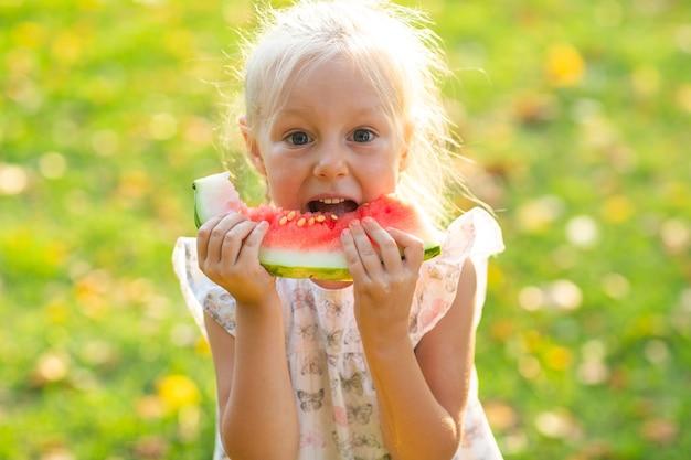 Śliczna blond dziewczynka je arbuza na trawie w parku