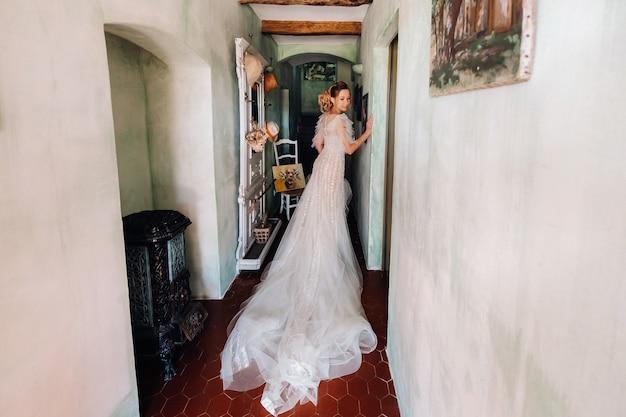 Śliczna blond panna młoda z miłą piękną pannę młodą o przyjemnych rysach w sukni ślubnej pozuje we wnętrzu pokoju. portret panny młodej w prowansji. francja.