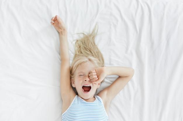 Śliczna blondynka mała dziewczynka rozciągający się w białym łóżku