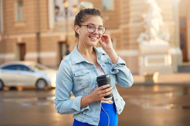 Śliczna blondynka młoda kobieta w okularach spaceruje po mieście ubrana niedbale w dżinsową kurtkę