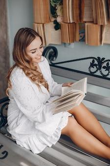 Śliczna blondynka w białej bluzce w domu