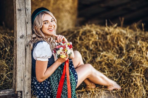 Śliczna blondynka w dirndl, tradycyjna festiwalowa suknia z bukietem śródpolni kwiaty siedzi na drewnianym ogrodzeniu przy gospodarstwem rolnym