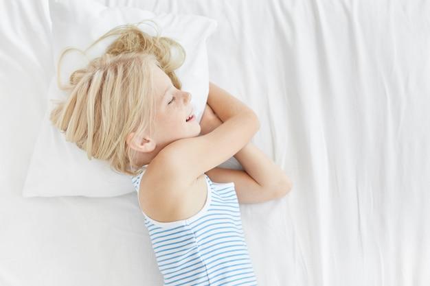 Śliczna blondynka w marynarskim t-shircie, leżąca na białej poduszce, uśmiechnięta we śnie, widząc przyjemne sny. spokojne dziecko płci żeńskiej śpi po ciężkim dniu gry z przyjaciółmi. dzieci, relaks