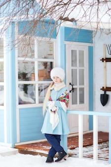 Śliczna blondynka w niebieskim płaszczu, białym futrzanym kapeluszu i szaliku w zimie. dziewczyna na werandzie domu. zimowy dom model pozowanie na ulicy. pojęcie ferii zimowych. szal malowany po rosyjsku