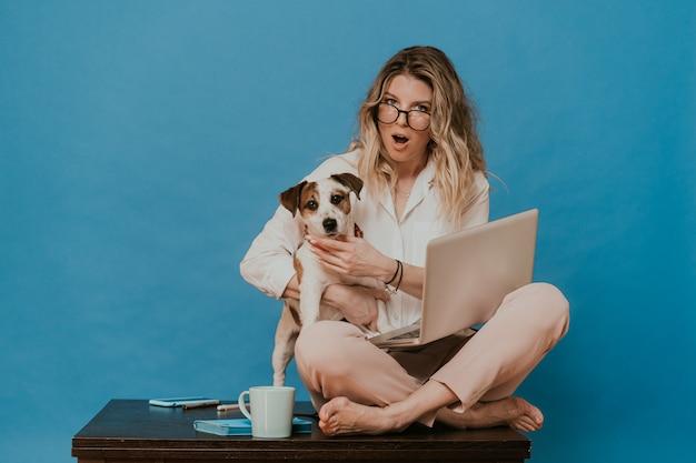 Śliczna blondynka w okularach, ubrana w białą koszulę i jasnoróżowe spodnie, siedząca na stole z laptopem, przytulająca swojego szczeniaka jacka russella, wygląda zszokowana wiadomością z szeroko otwartymi oczami i ustami.