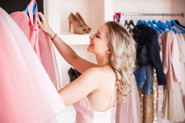 Śliczna blondynka w różowej piżamie wybrała spódnicę i garderobę i uśmiecha się.
