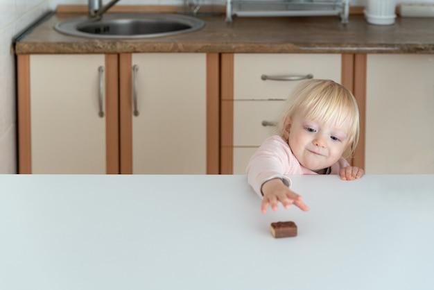 Śliczna blondynka wyciąga rękę do cukierka leżącego na stole.