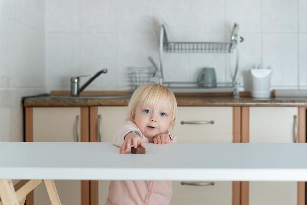 Śliczna blondynka wyciąga rękę do cukierków na stole.