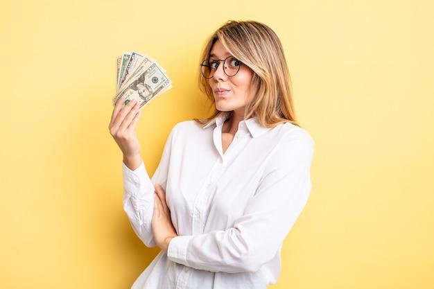 Śliczna blondynka wzrusza ramionami, czując się zdezorientowana i niepewna. koncepcja banknotów dolarowych