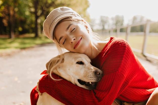 Śliczna blondynka z ukochanym psem spędza razem czas na świeżym powietrzu jesienią. ładny portret pięknej kobiety i jej zwierzaka w parku.