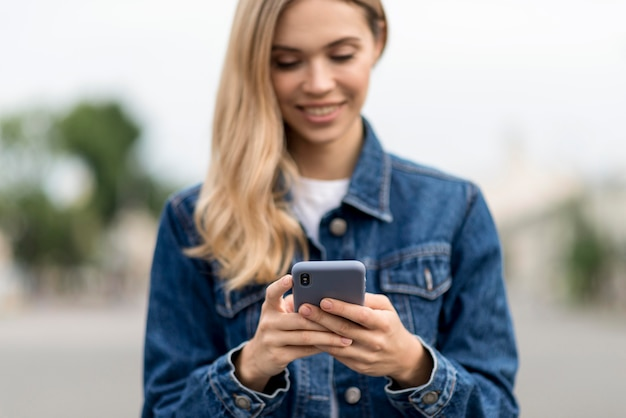 Śliczna blondynka za pomocą swojego telefonu komórkowego