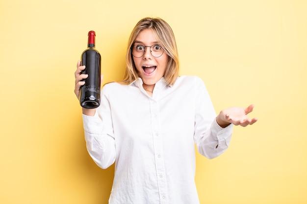 Śliczna blondynka zachwycona, zszokowana i zdumiona niesamowitą niespodzianką. koncepcja butelki wina