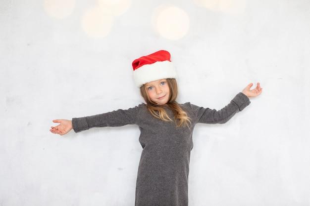 Śliczna blondynki dziewczyna jest ubranym santa claus kapelusz