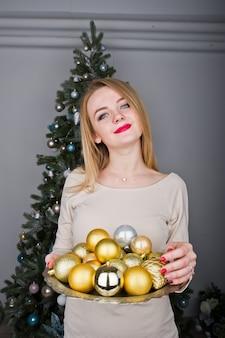 Śliczna blondynki dziewczyna na beż sukni przeciw nowego roku drzewu zz złotymi nowy rok piłkami przy studiiem
