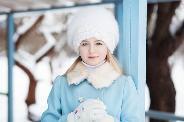 Śliczna blondynki dziewczyna w błękitnym żakiecie i białym futerkowym kapeluszu w zimie. śnieżna pogoda. dziewczyna na werandzie domu. pojęcie ferii zimowych. zakończenie portret blondynki dziewczyny twarz.