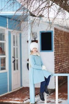 Śliczna blondynki dziewczyna w błękitnym żakiecie i białym futerkowym kapeluszu w zimie. śnieżna pogoda. dziewczyna na werandzie domu. zimowy dom model pozowanie na ulicy. pojęcie ferii zimowych.