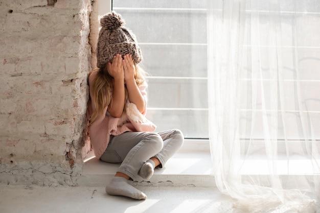 Śliczna blondynki dziewczyna zakrywa jej twarz