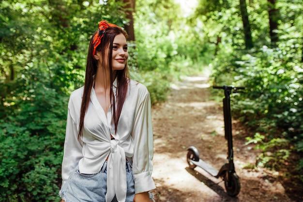 Śliczna brunetka dziewczyna jeździ na hulajnodze elektrodowej w parku, w której ma na sobie białą koszulę. koncepcja ekologicznego transportu i wynajmu.