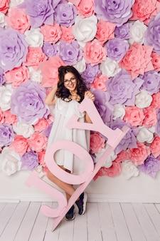 Śliczna brunetka dziewczyna stoi i trzyma drewniane słowo radość, uśmiechając się szeroko. ma różowe tło w kwiatach. bawi się włosami