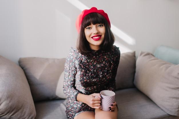 Śliczna brunetka dziewczyna w czerwonym berecie siedzi na szarej kanapie z filiżanką herbaty i uśmiecha się. urocza młoda kobieta z krótkimi włosami w stylowe ubrania, pozowanie, relaksując się na krześle podczas przerwy na kawę.