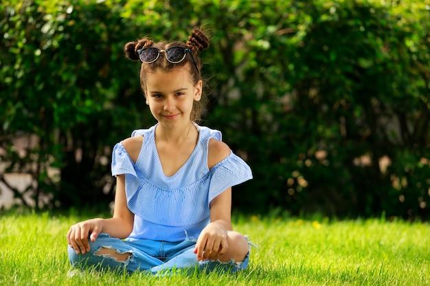 Śliczna brunetka dziewczyna w niebieskiej bluzce siedzi na trawie w lecie. zdjęcie wysokiej jakości