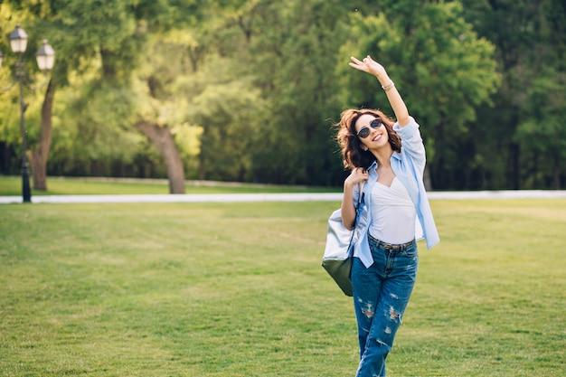 Śliczna brunetka dziewczyna z krótkimi włosami w okulary pozowanie w parku. nosi białą koszulkę, niebieską koszulę i dżinsy, torbę. trzyma rękę w górze i uśmiecha się.