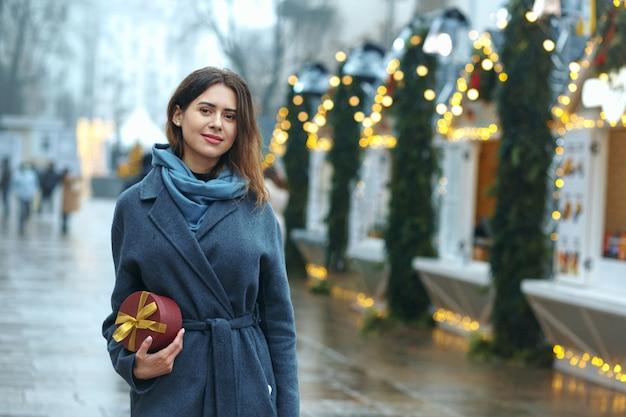 Śliczna brunetka kobieta trzyma pudełko w pobliżu jarmarku bożonarodzeniowego. miejsce na tekst