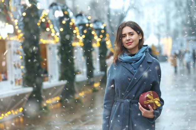Śliczna brunetka kobieta trzyma pudełko w pobliżu jarmarku bożonarodzeniowego podczas opadów śniegu. miejsce na tekst