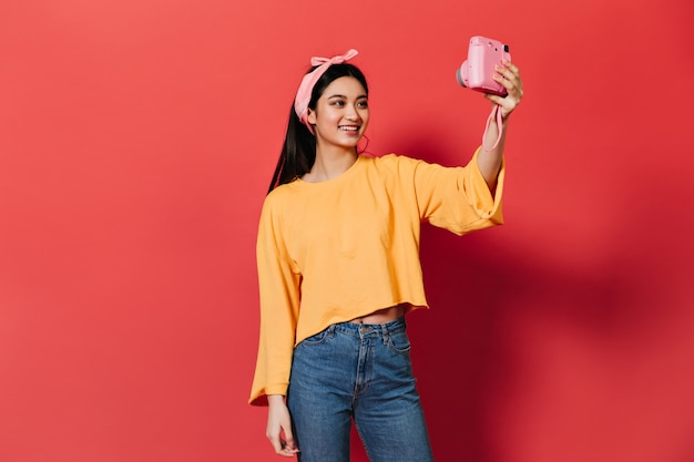 Śliczna brunetka kobieta uśmiecha się i robi selfie na różowym froncie