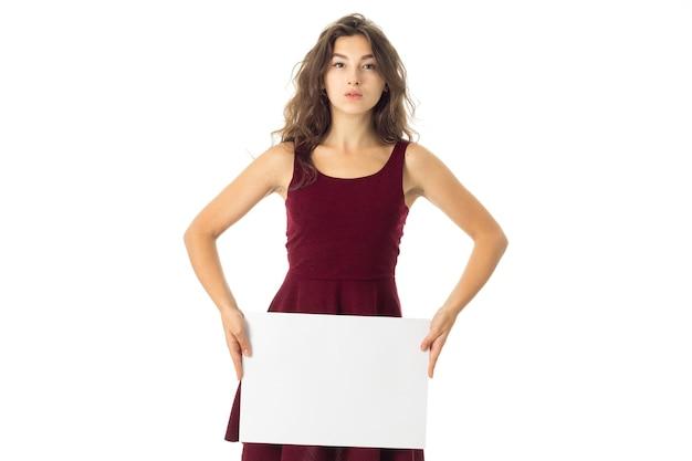 Śliczna brunetka młoda kobieta w czerwonej sukience z białą tabliczką w rękach na białym tle
