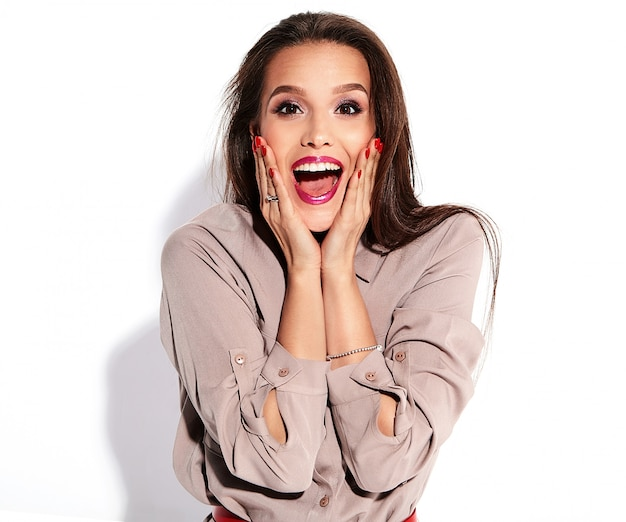 Śliczna brunetka modelka w swobodnych beżowych ubraniach z jasnym makijażem i czerwonymi ustami, zakrywającymi twarz rękami