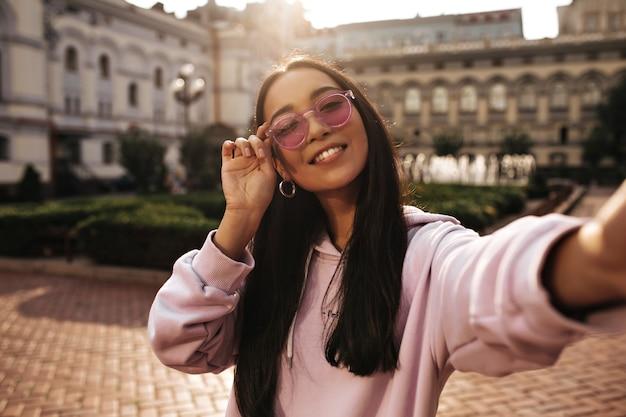 Śliczna brunetka nastolatka w różowej bluzie z kapturem i stylowych okularach przeciwsłonecznych szczerze się uśmiecha, patrzy z przodu i robi selfie na zewnątrz
