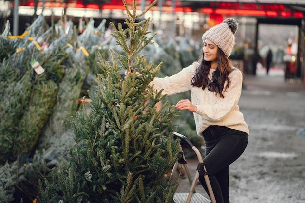Śliczna brunetka w białym pulowerze z choinką