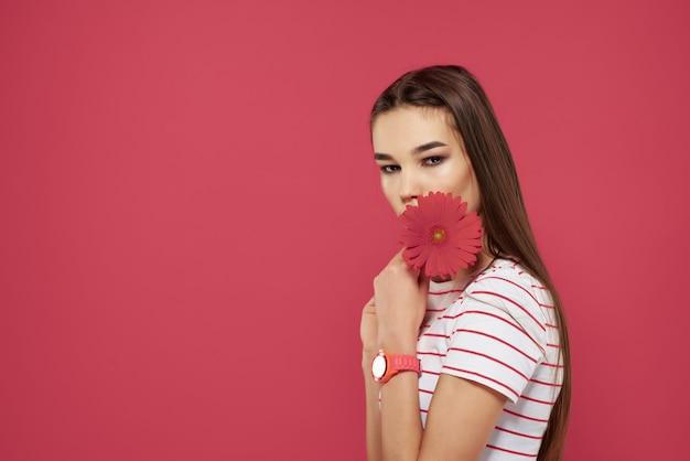 Śliczna brunetka w paski t-shirty czerwony kwiat romans moda różowe tło