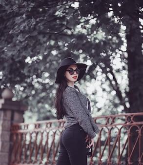 Śliczna brunetka z czerwonymi wargami w kapeluszu i okularach przeciwsłonecznych pozuje w mieście