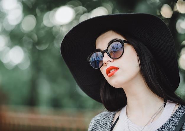 Śliczna brunetka z czerwonymi wargami w okularach przeciwsłonecznych pozuje w mieście