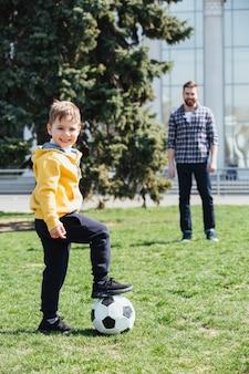 Śliczna chłopiec bawić się futbol z jego ojcem w parku