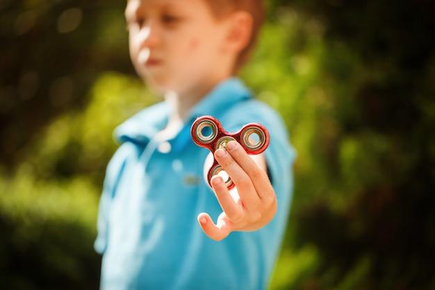 Śliczna chłopiec bawić się z fidget ręki kądziołkiem w letnim dniu. popularna i modna zabawka dla dzieci i dorosłych.