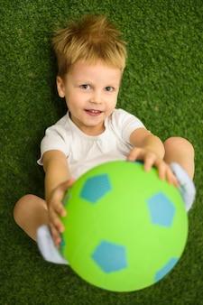 Śliczna chłopiec bawić się z futbolem
