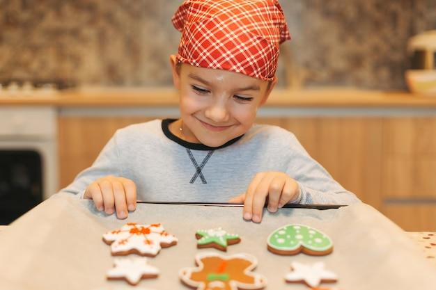 Śliczna chłopiec cieszy się smak świeżych wspieranych bożenarodzeniowych ciastka.